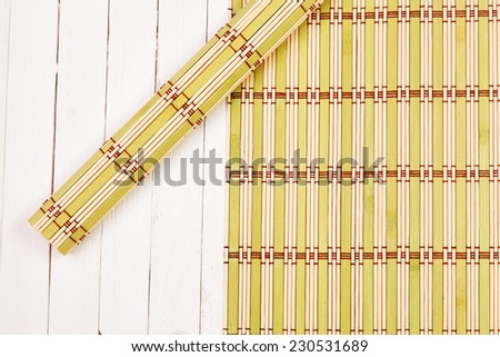 Color bamboo mat on wooden table - stock photo