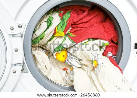 Color bed-clothes in the washing machine - stock photo