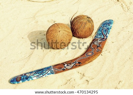 Color boomerang and two coconuts on a sandy beach taken closeup.Toned image.