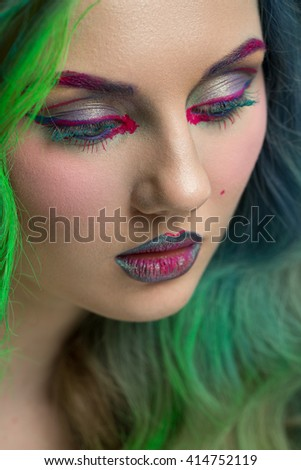 Color burst. Vertical cropped closeup of a green haired female model wearing multicolored art makeup looking away