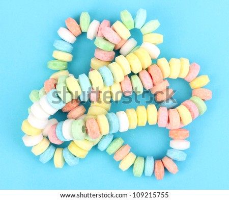 Color candies on rope on blue background - stock photo