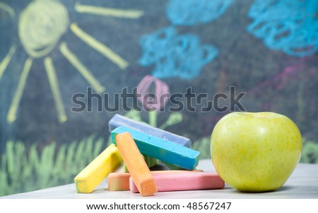 Color chalk and apple with kid picture on background - stock photo