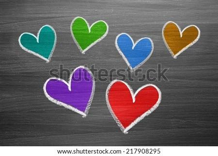 color chalk heart shapes on blackboard - stock photo