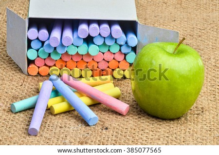 color chalks on gunny sack textile texture as teacher instruments in a classroom selective focus