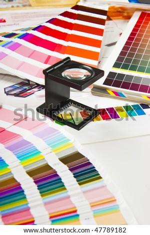 Color charts, magnifying glass and a printed sheet - stock photo