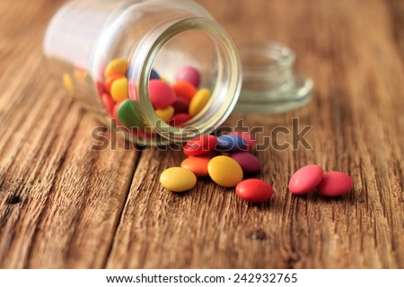 Color Chocolate smarties spilled out from glass dose on old worn wooden board and with glass cap in background - stock photo
