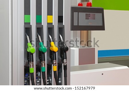 Color coded fuel nozzles at petrol station - stock photo