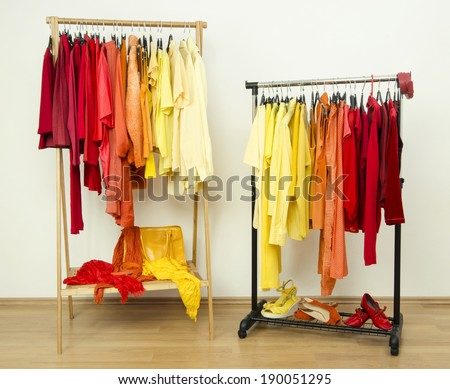 Color coordinated clothes on hangers. Shades of yellow, orange and red clothes hanging on a rack nicely arranged.