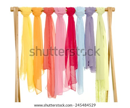 Color coordinated scarves arranged on a rack. All colors women scarves isolated on white. - stock photo