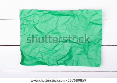 color crumpled paper on white wooden background. Green color. - stock photo