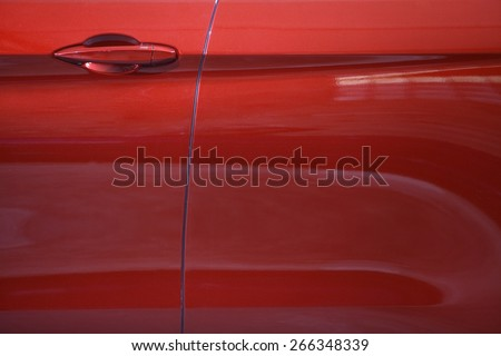 Color detail of a red car door handle. - stock photo