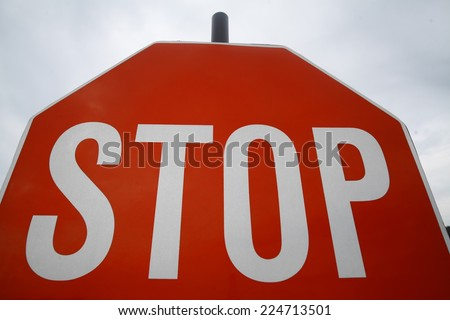 "Color detail of a red ""STOP"" sign at a road junction. - stock photo"