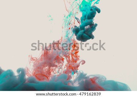 Color drop underwater creating a silk drapery. Ink swirling underwater. Cloud of colorful shiny ink isolated on black background.