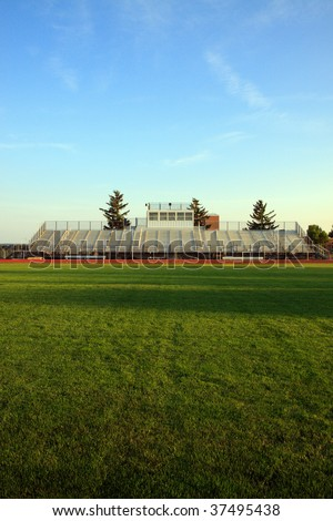 Color DSLR image of American sport football bleachers and green grass ball field. Dusk with a blue sky. Vertical with copy space for text. - stock photo