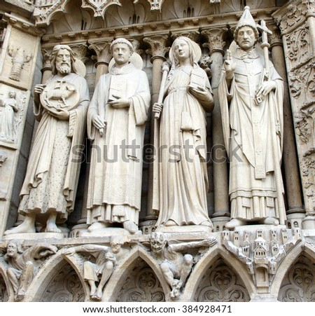 Color DSLR image of ancient carvings and statues above the doors of the Catholic Cathedral Notre Dame, Paris France. The historic church is popular with tourists and religious pilgrims. - stock photo