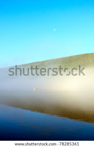 Color DSLR image of Canadice Lake, a New York Finger Lake, at dawn, with mist and a boater through the fog over still, calm water. Vertical with copy space for text. - stock photo