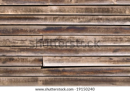 Color DSLR image of old, weathered red and brown cedar siding or panelling. Horizontal orientation with copy space for text. - stock photo