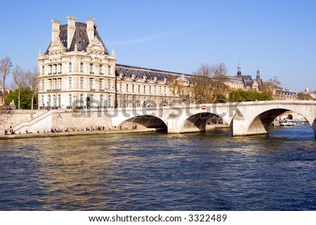 Color DSLR image of the Louvre Museum in the sunlight, across the Seine River, Paris, France.  The landmark is a popular tourist attraction with world famous art. Horizontal with copy space for text.