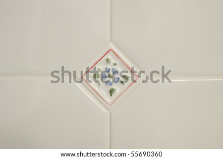 Color DSLR image of white Bathroom tiles; in horizontal orientation and a blue flower decorative tile in the center. Copy space for text. - stock photo