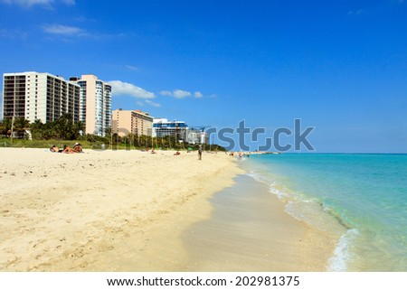 Color DSLR landscape of luxury condominiums on the beach, South Beach, Miami, Florida.  The condos tower over the sand, with a blue sky and water.  The image is horizontal with copy space for text. - stock photo