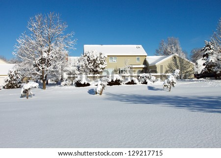 Color DSLR landscape picture of a suburban colonial house covered in white winter snow.  The home is seen from the backyard, in horizontal, with a blue sky background and ample copy space for text. - stock photo