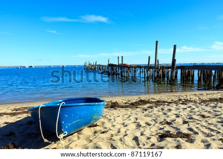 Color DSLR picture of a blue boat on the beach sand in Provincetown, Massachusetts.  There is an old, broken dock and water in the background.  In horizontal orientation with copy space for text. - stock photo
