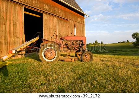 Color DSLR picture of an antique red farm tractor in front of wood barn.  Golden sunset light and green grass.  Horizontal orientation with copy space for text