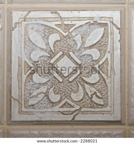 Color DSLR picture of square off white, tan or beige decorative ceramic tile with a textured pattern. - stock photo