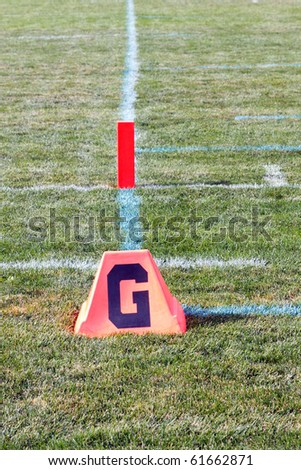 Color DSLR picture of the goal line on an American sports football field.  Crossing this line scores a touchdown and is the objective of game. Vertical orientation with copy space for text - stock photo