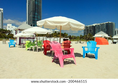 Color DSLR picture of vivid adirondack beach chairs and umbrellas on South Beach, Miami, Florida.  High rise condominiums and a blue sky background.   The horizontal image has copy space for text - stock photo