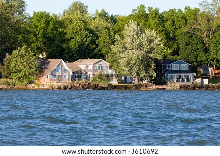 Color DSLR wide angle view of a summer vacation lake house on Ontario Lake, with water in the foreground and trees in the background. Horizontal with copy space for text.