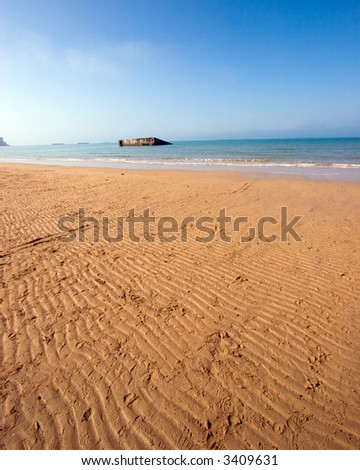 Color DSLR wide angle view of Mulberry Harbor, Normandy beach, France. Coast was used in WWII D-Day Invasion. Rippled sand in the foreground and English Chanel water and blue sky background. Vertical - stock photo