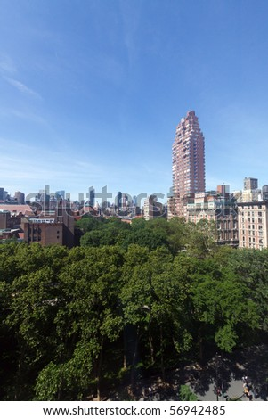 Color DSLR wide angle view of Upper West Side of Manhattan apartment buildings, from height of about 10 stories; green trees in foreground and blue sky background. Vertical with copy space for text