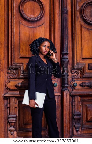 Color #2E1A47 filtered look. African American Businesswoman working in New York. Young black female lawyer with braid hairstyle standing by doorway, carrying laptop computer, listening cell phone. - stock photo