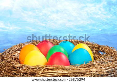 color eggs in a golden nest on blue sky background