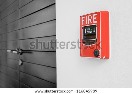 color fire alarm switch on black and white wall - stock photo