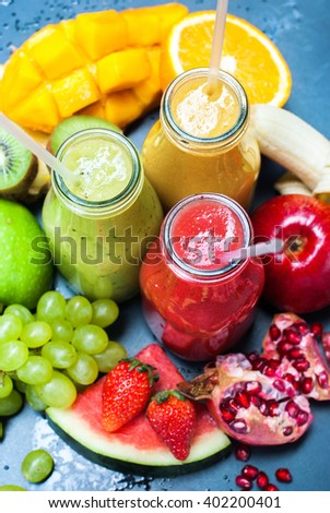 Color Fresh Juices Smoothie Bottles Red Green Orange Tropical Fruits Selective Focus Black Background Healthy Beverage Top View - stock photo