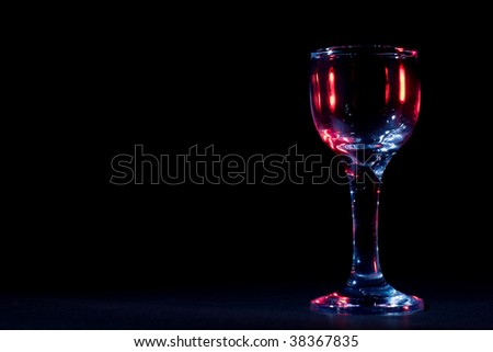 Color glares on wine glass in the dark - stock photo