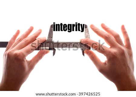 """Color horizontal shot of two hands holding a caliper and measuring the word """"integrity"""". - stock photo"""