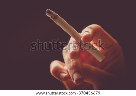 Color image of a hand holding a cigarette. - stock photo
