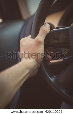 Color image of a hand holding a steering wheel inside a car.