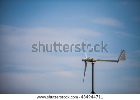 Color image of a wind vane on a sunny day.
