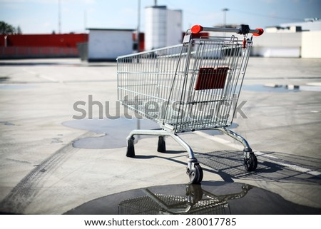 Color image of an abandoned shopping trolley in a parking lot. - stock photo
