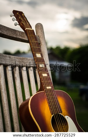 Color image of an old wooden acoustic guitar leaning against an old wooden rocking chair at sunset in Clarksdale Mississippi