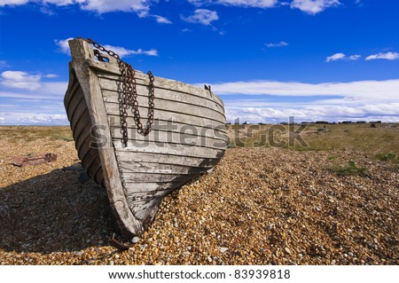 color image of an old wooden fishing boat left to rot and decay on the shingle beach at Dungeness, England, UK.