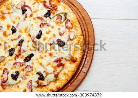 color image of fresh tasty pizza on wooden plate