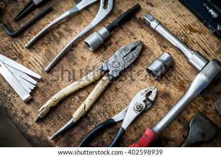 Color image of many tools on a wooden plank. - stock photo