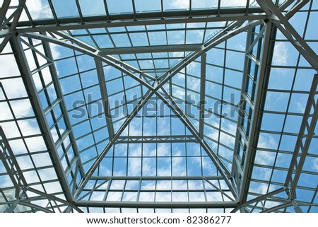 Color image of the glass roof of a mall with bright blue sky with clouds - stock photo