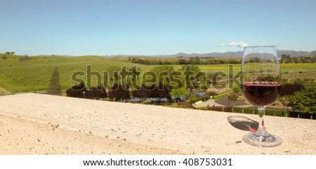 color landscape stock photo of glass of red wine on balcony overlooking Napa Valley wine country vineyards with a lake and willow trees in foreground and vineyards in background - stock photo