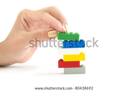 color lego bricks with hand isolated on white - stock photo
